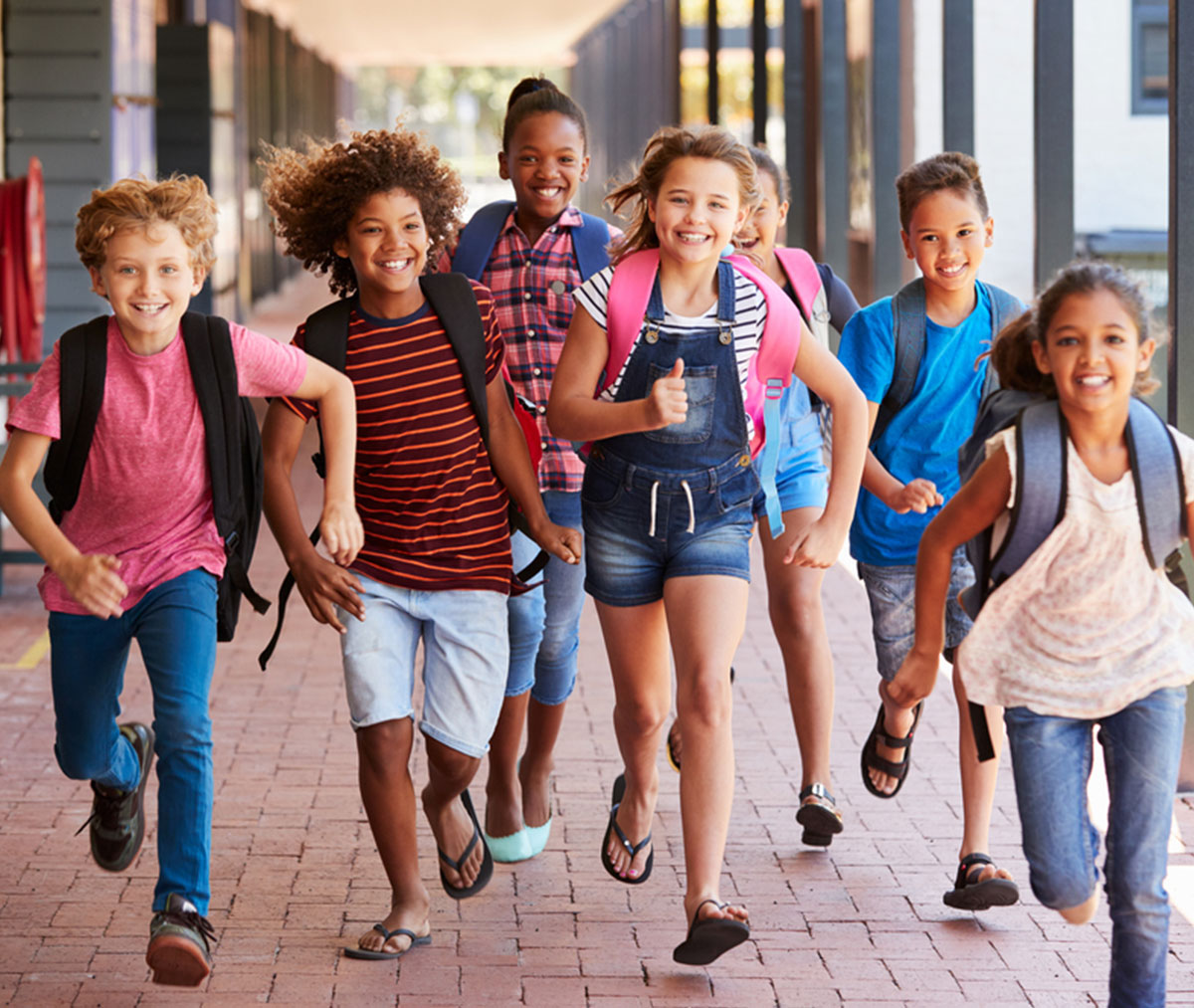 group of young school kids running with backpacks on