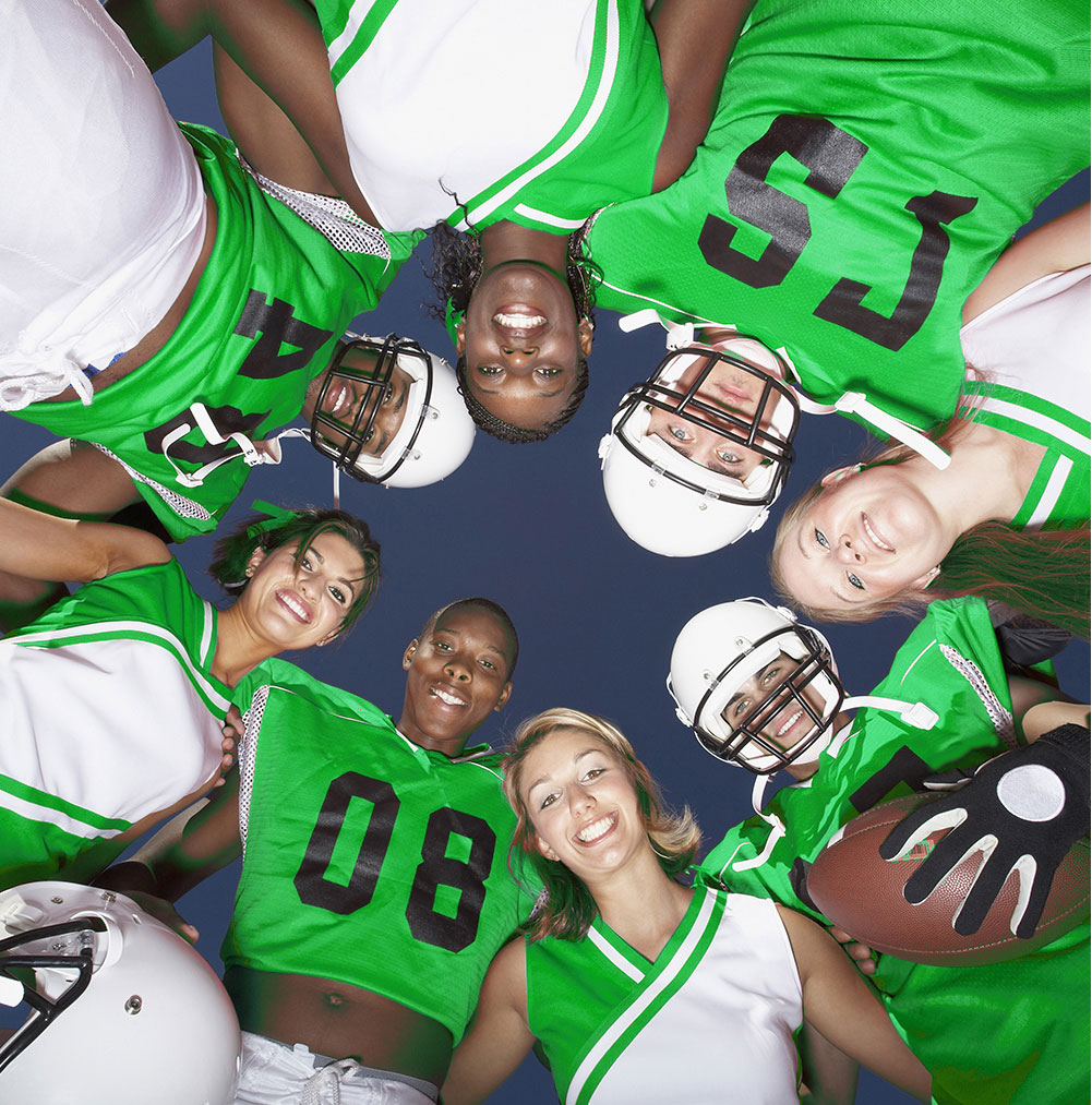 Football players and cheerleaders in green uniforms huddled together and smiling