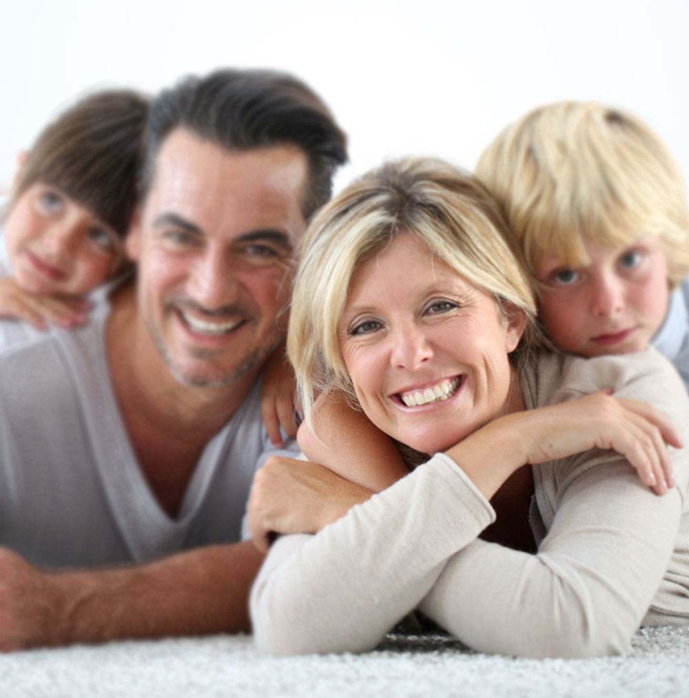 family of four laying on the floor and smiling