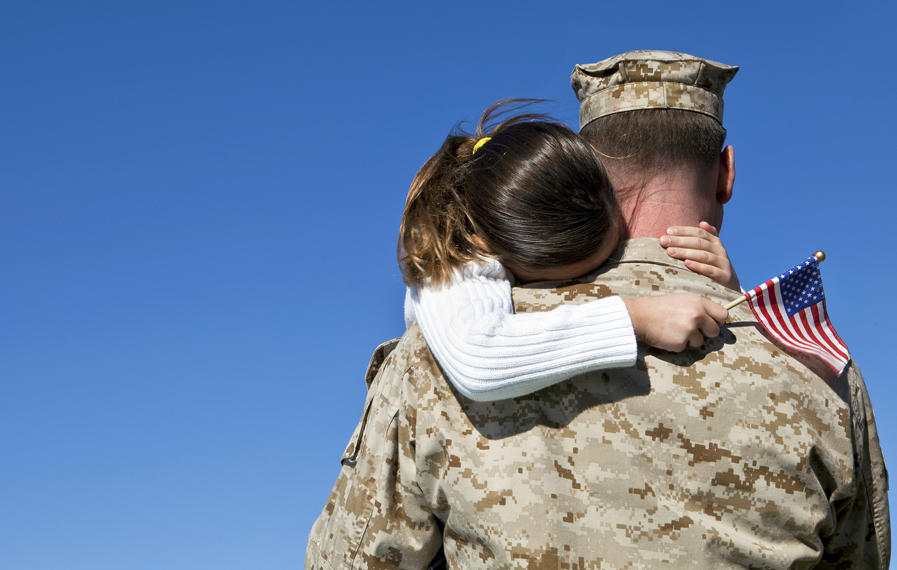 U.S. military man hugs his daughter as he holds an american flag