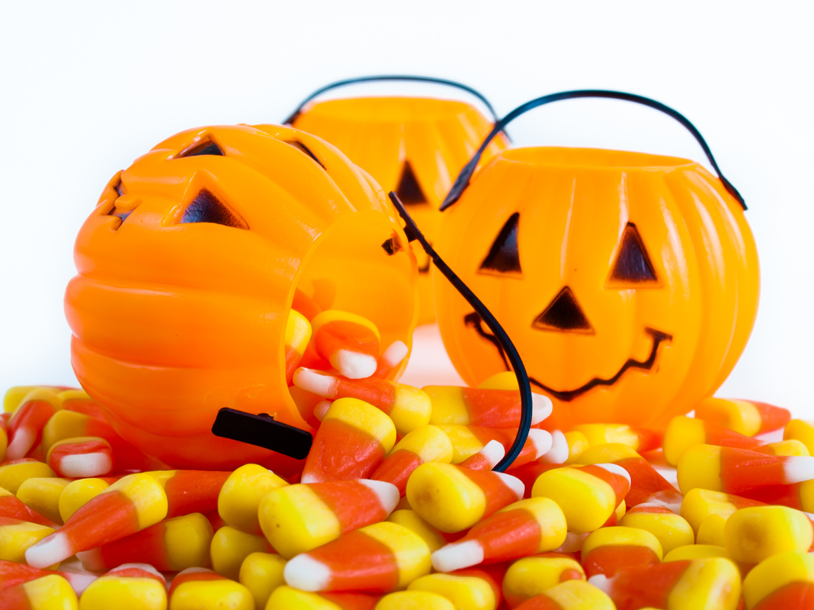 three jack o'lantern candy buckets spilling out a pile of candy corn